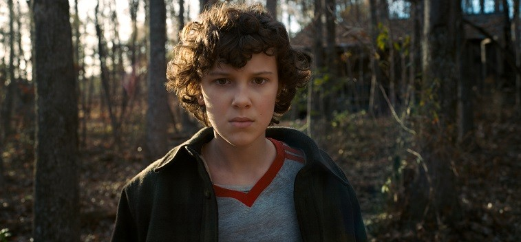 Eleven stands in the woods and stares ahead in Stranger Things 2