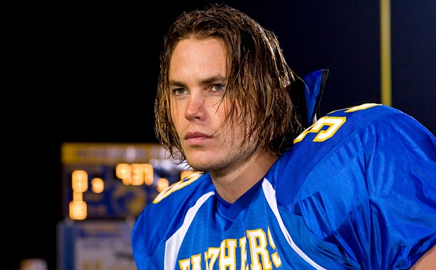 Taylor Kitsch in a football jersey