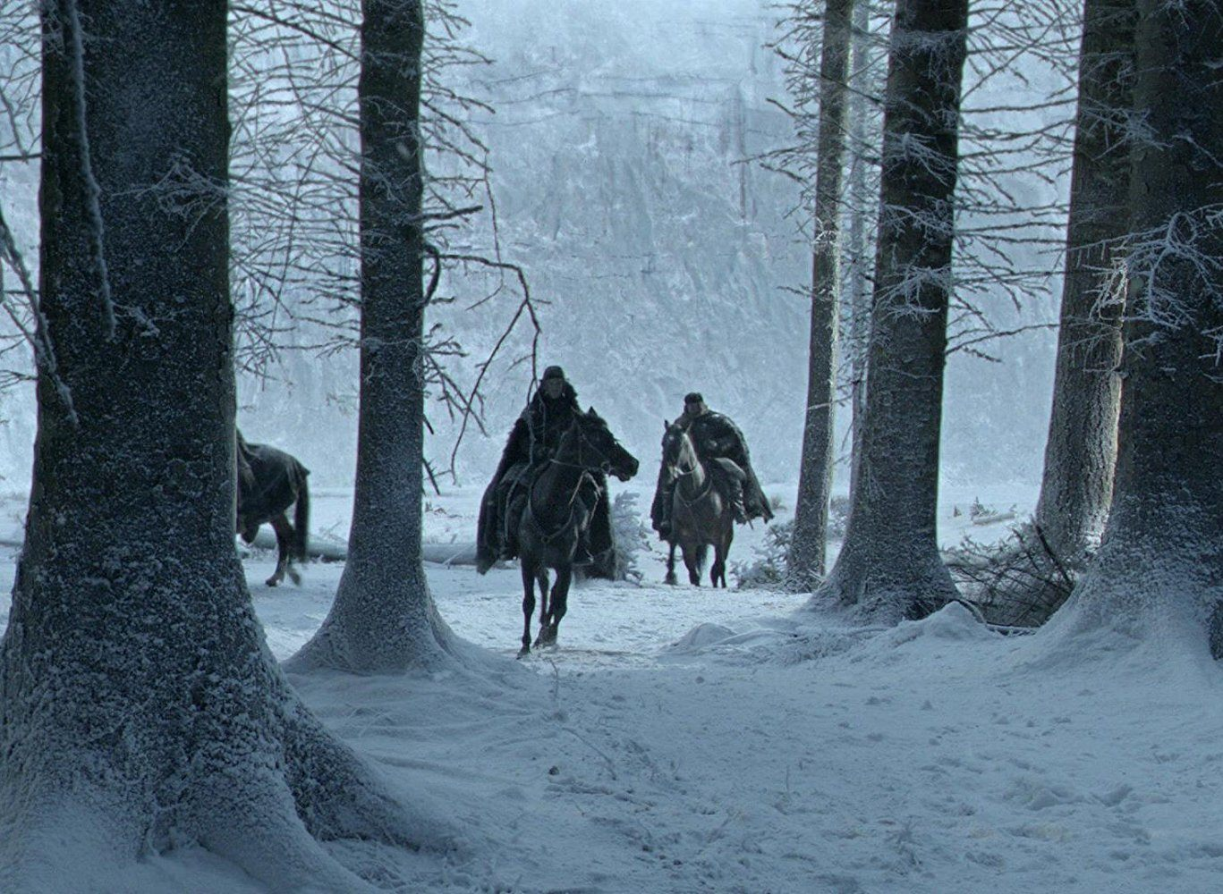 Men riding horses in the woods where snow has fallen.