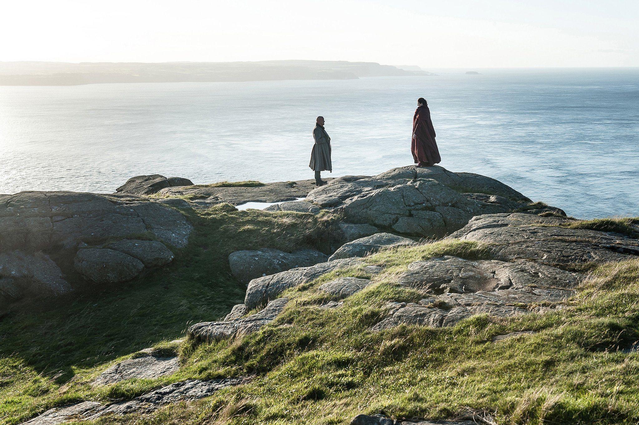 Varys and Melisandre speak on a cliff beside the ocean