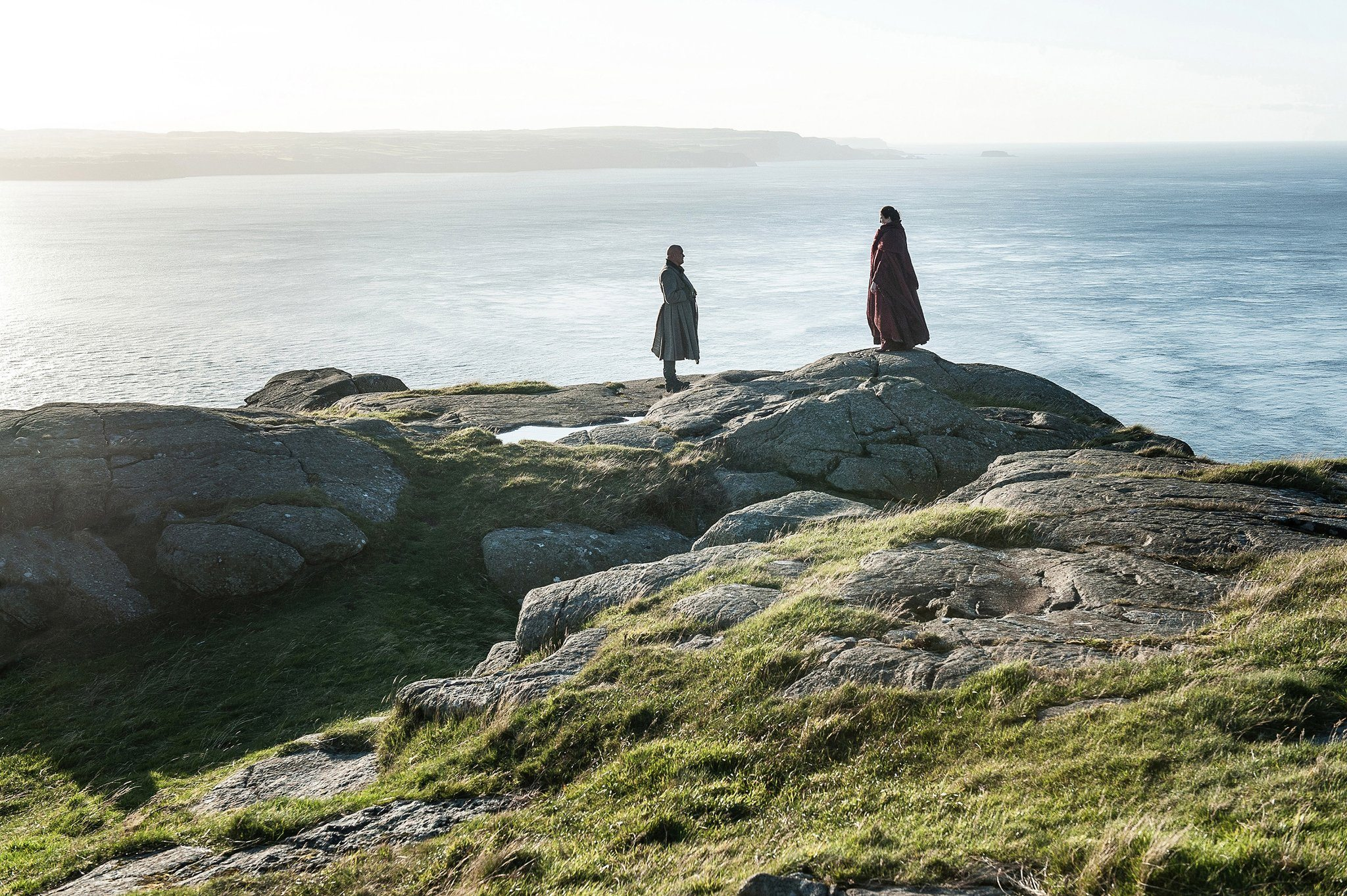 Varys and Melisandre speak on a cliff beside the ocean