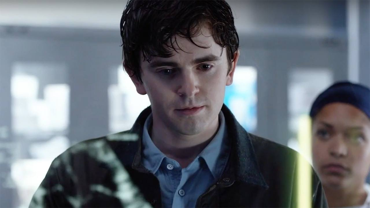 A boy in a blue shirt and green jacket looks through a hospital window
