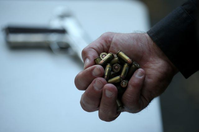 A man holds bullets in his hand.