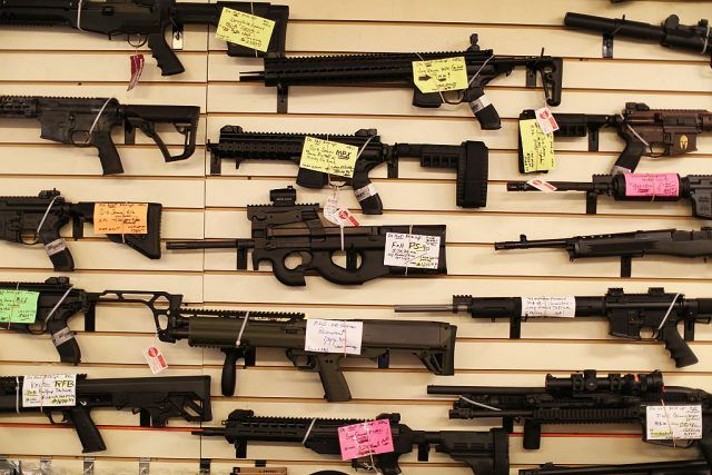 Guns and rifles lined up on a wall.