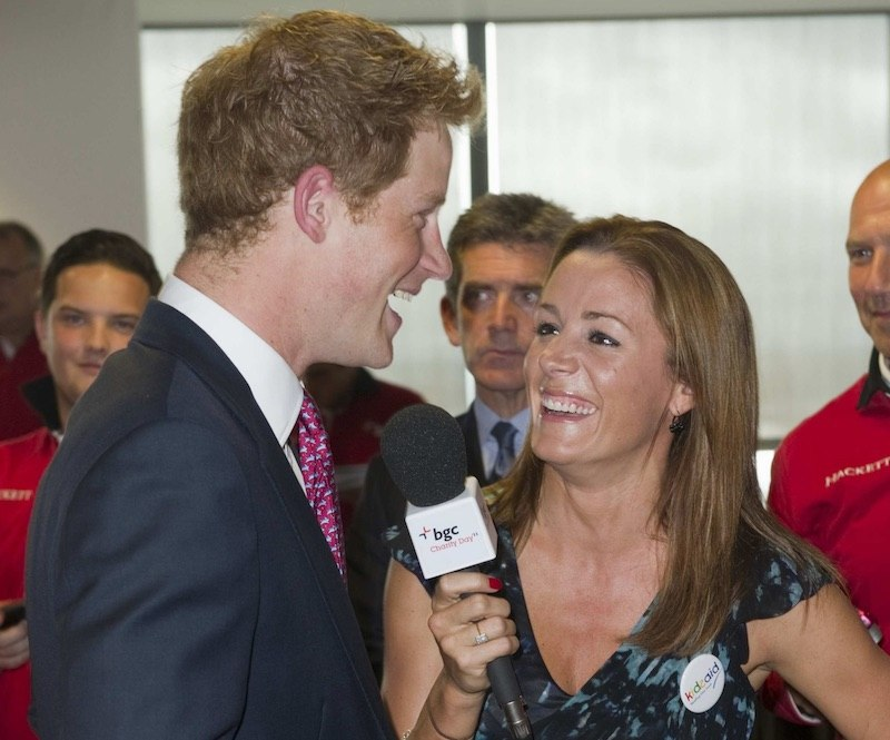 Natalie Pinkman holds up a microphone as Prince Harry speaks into it