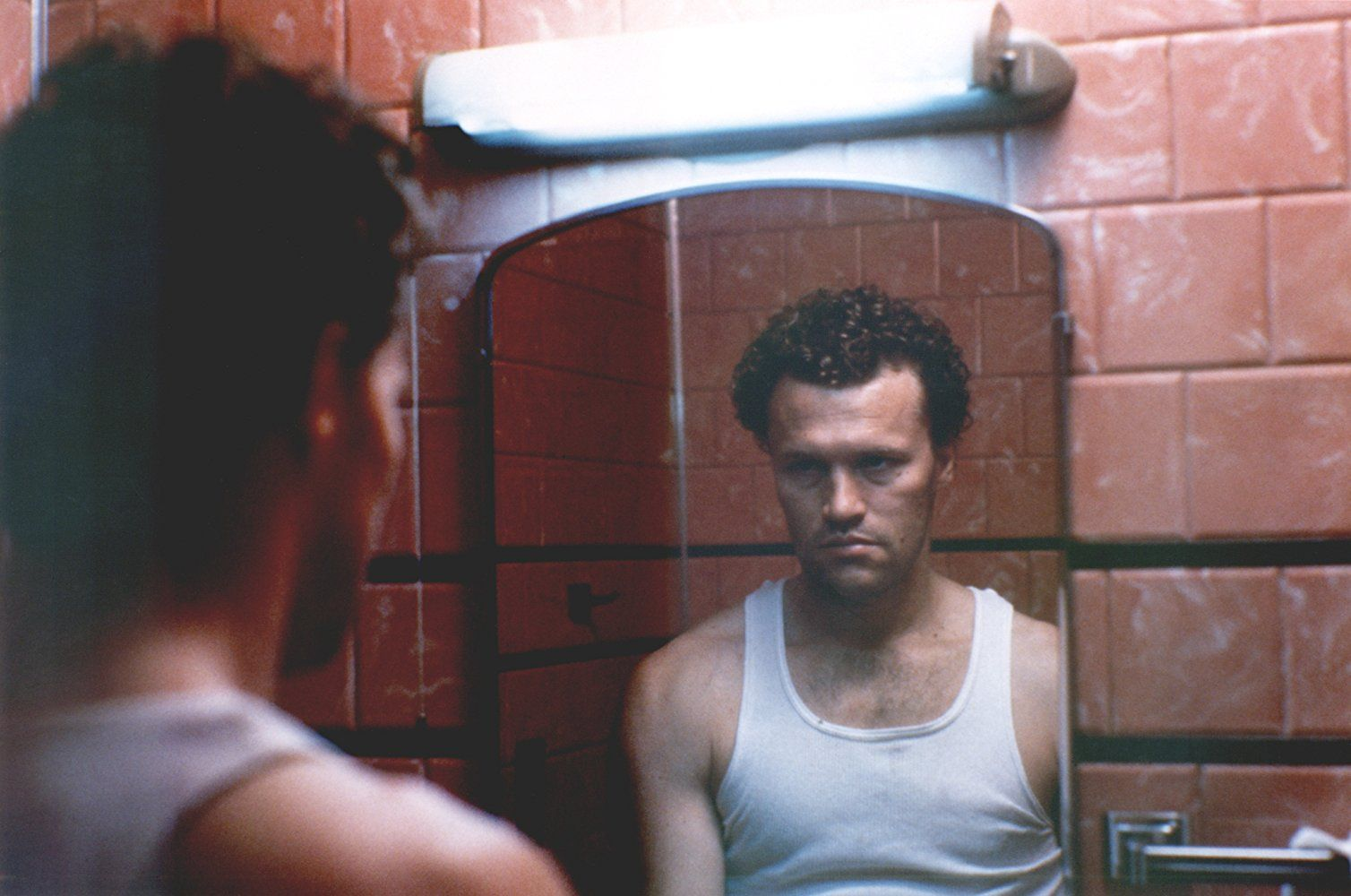 Michael Rooker in Henry: Portrait of a Serial Killer looking at himself in the mirror