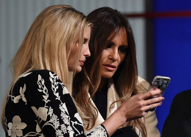 Donald Trump's wife Melania Trump (R) and daughter Ivanka look at a smartphone