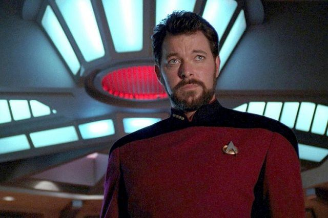 William T. Riker stands in a red and black uniform inside a ship.
