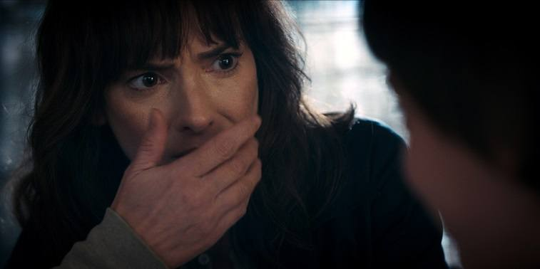 Joyce Byers holds a hand up to her mouth in Stranger Things 2