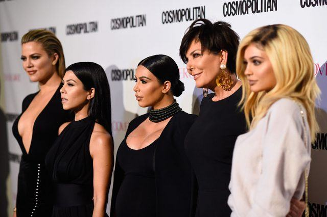 Khlóe Kardashian on a red carpet with her family.