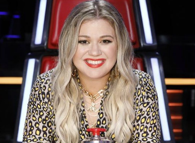 Kelly Clarkson sits on a red The Voice chair