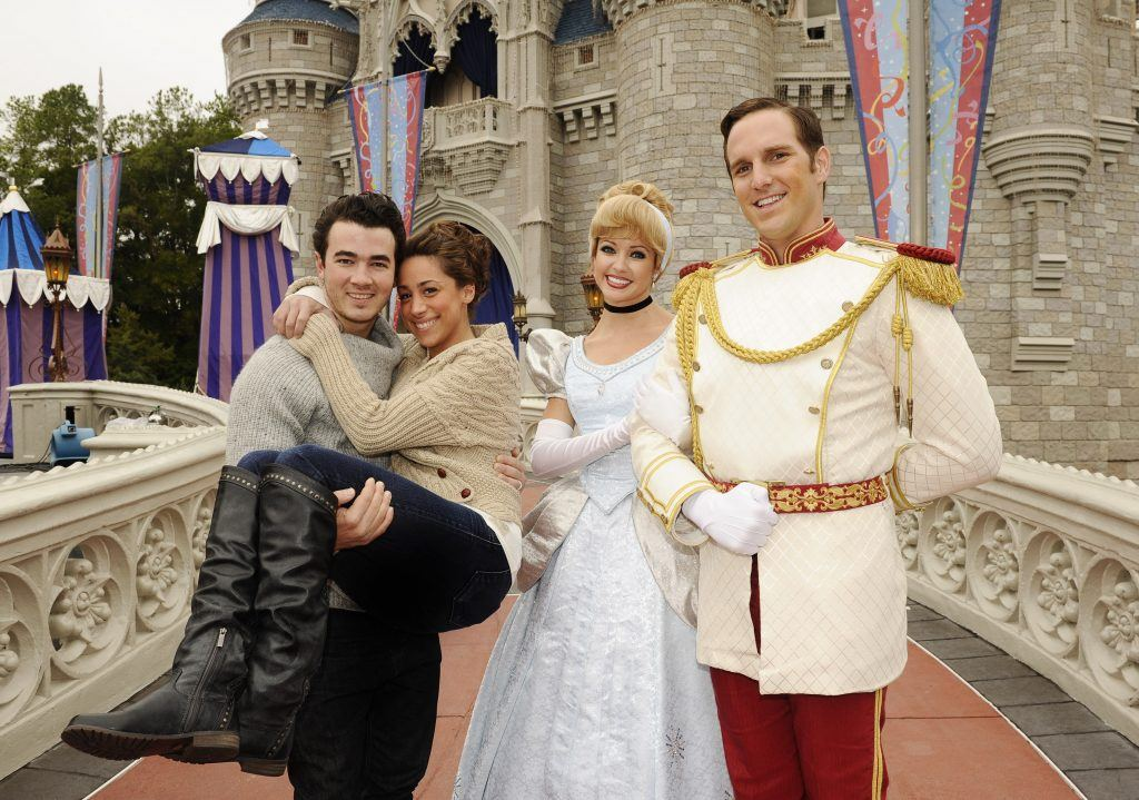 Kevin Jonas at Disney World standing with Cinderella and Prince Charming