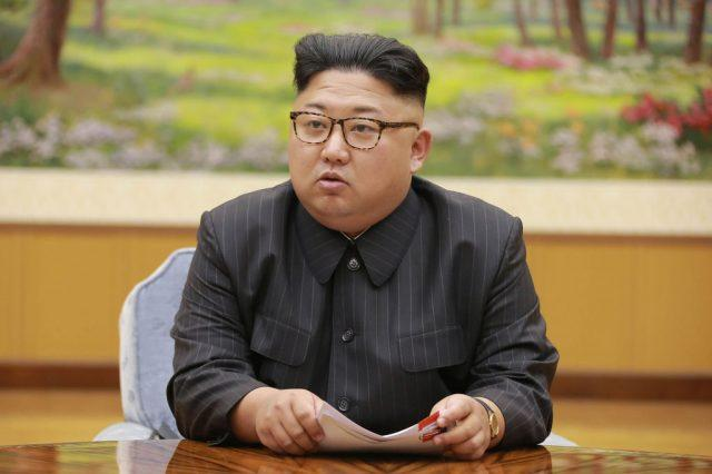 Kim Jong Un sitting at a desk while holding documents.
