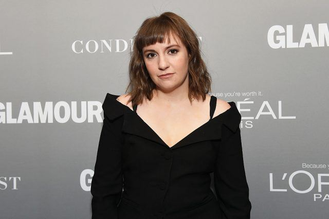 Lena Dunham poses in a black dress on a red carpet.