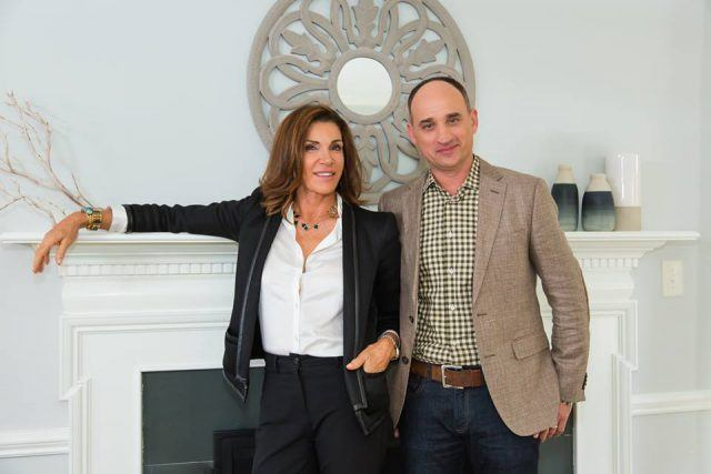 The hosts of 'Love It or List It' in front of a fireplace.