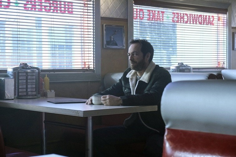 Luke Perry's Fred Andrews sits at a table holding a mug in Riverdale