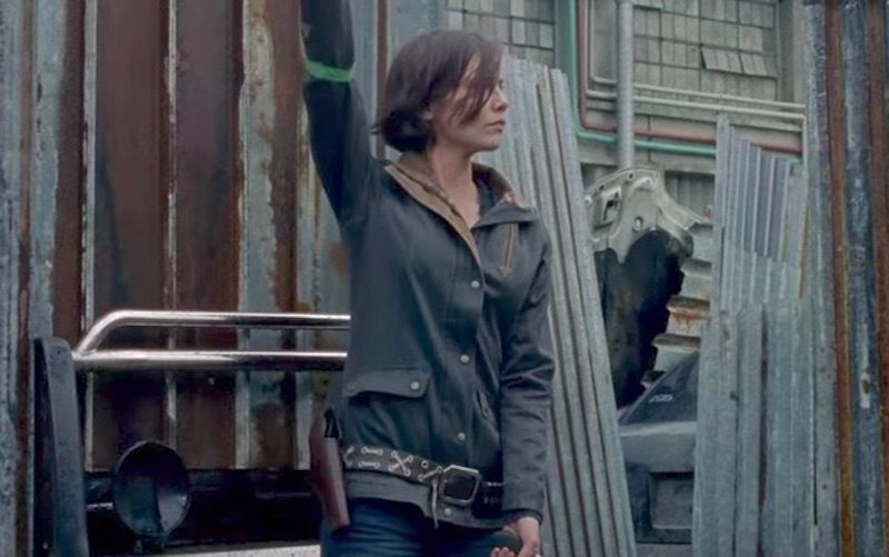 Maggie lifts her arm while standing in front of a wall