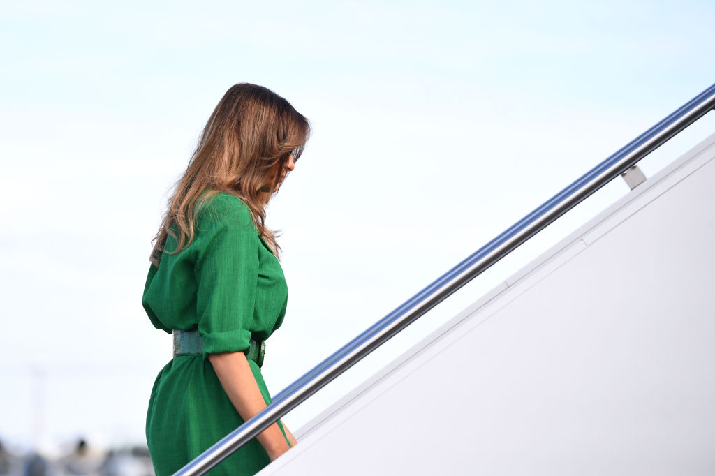 Melania Trump climbing steps towards an airplane.