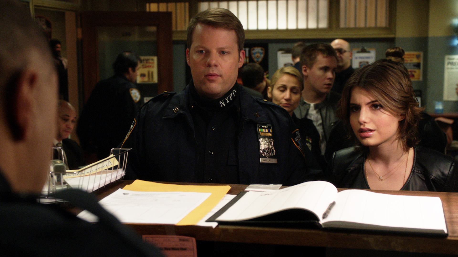 Sami Gayle as Nicky stands next to a police officer in a police station on Blue Bloods