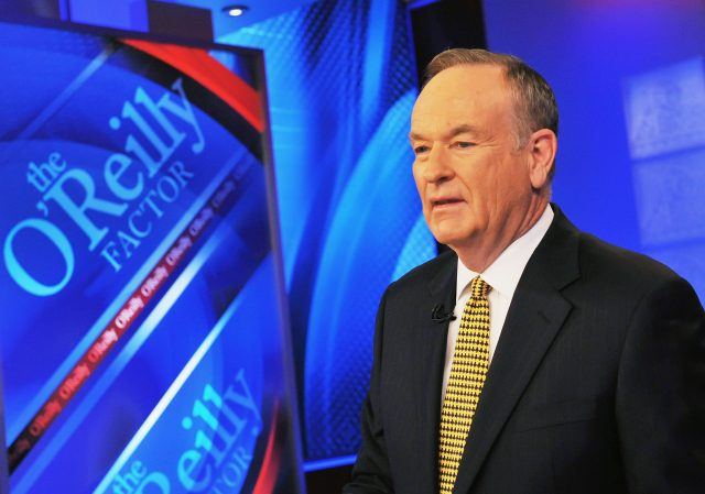 "Bill O'Reilly, host of FOX's ""The O'Reilly Factor"" sitting in a suit in front of a desk."