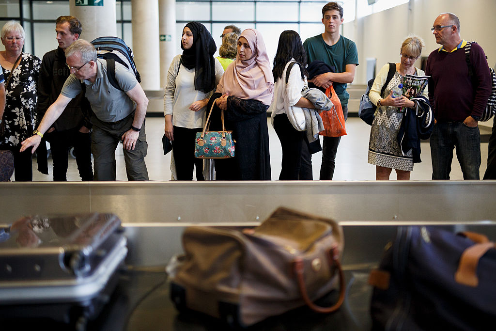 Passengers waiting for luggage at baggage claim.