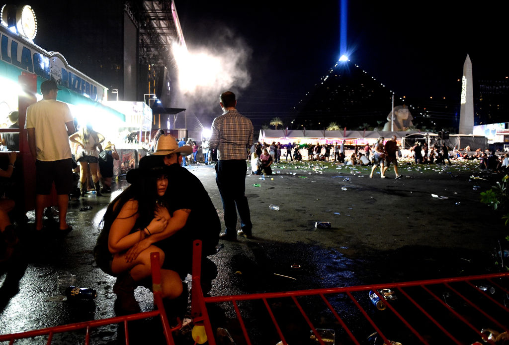 Two people crouch down in the crowd after the Las Vegas shooting