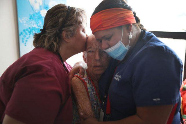 Two nurses support an elderly patient.