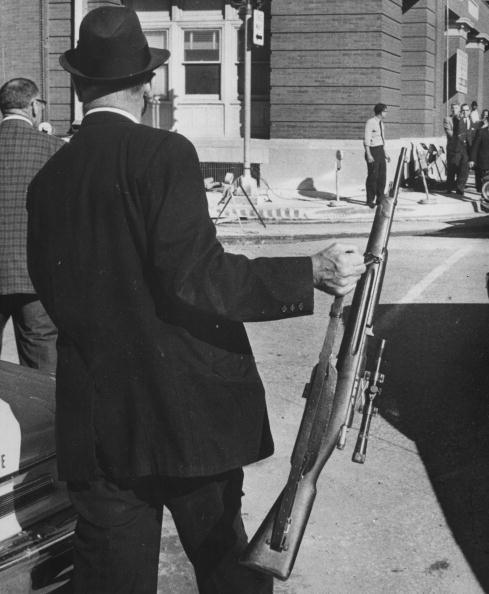 A man holding the rifle used by Lee Harvey Oswald in his assassination.
