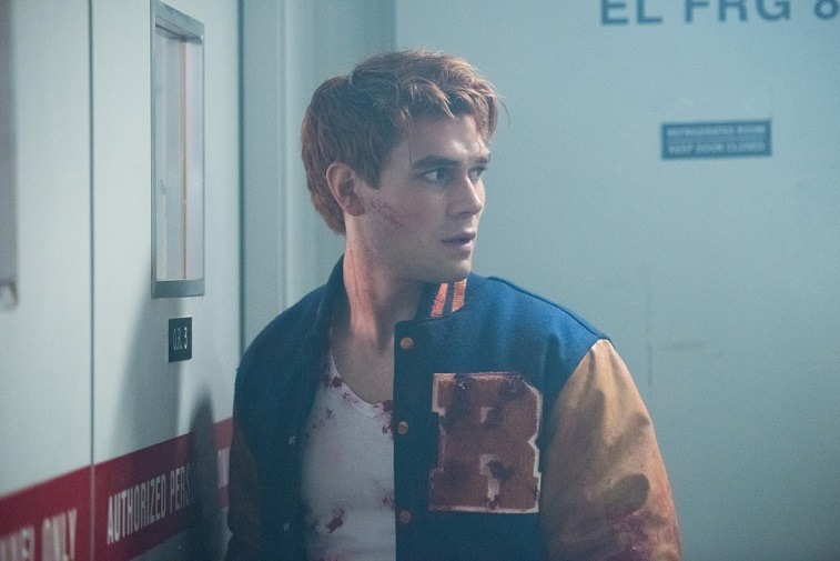 K.J. Apa as Archie Andrews wears a bloodied white tank and letterman jacket in Riverdale