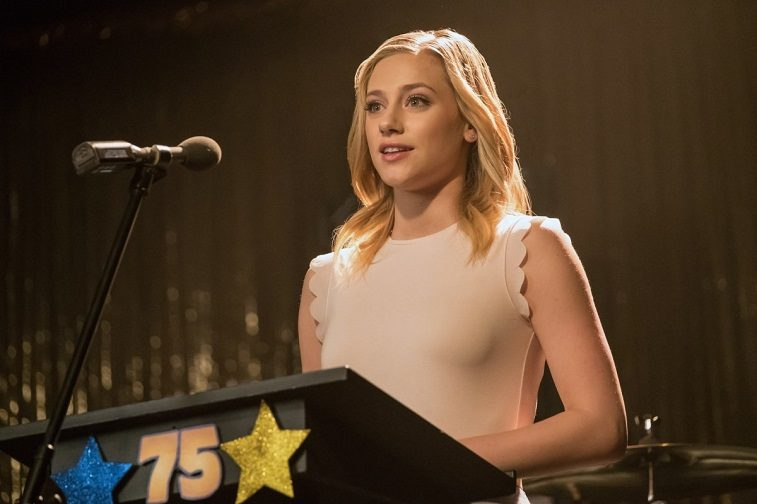 Lili Reinhart as Betty Cooper stands at a podium in front of a microphone in Riverdale