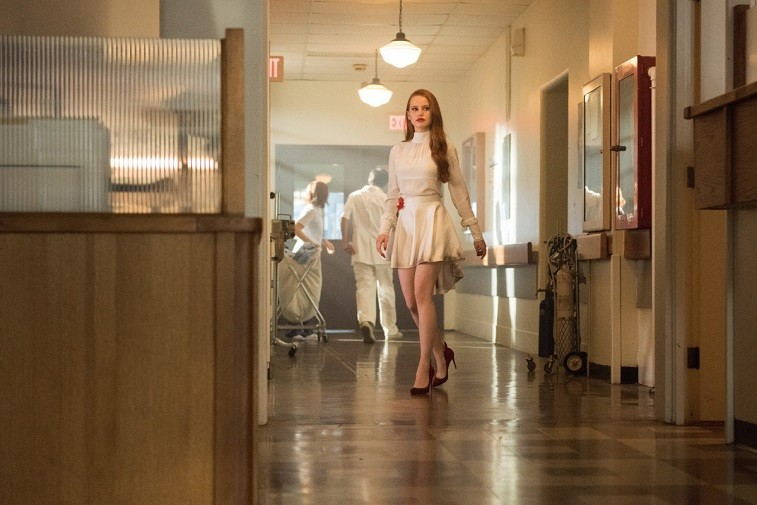 Madelaine Petsch as Cheryl Blossom wears a white dress and walks in a hospital in Riverdale
