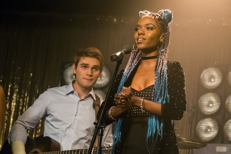 Ashleigh Murray as Josie McCoy stands at a microphone in Riverdale
