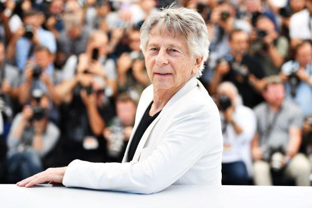 Roman Polanski standing in front of a group of photographers at the Cannes Film Festival.