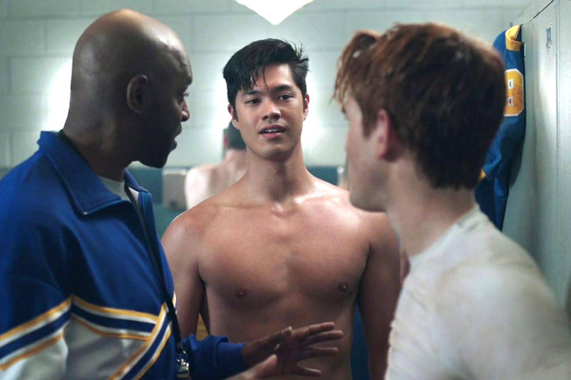 Ross Butler stands shirtless in between two men on Riverdale