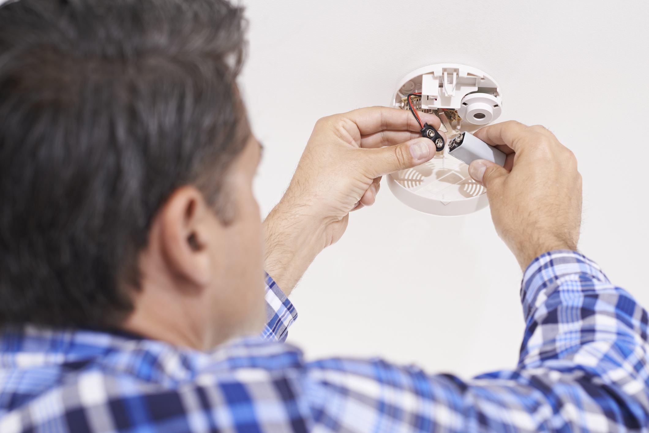 Man replacing battery in smoke detector