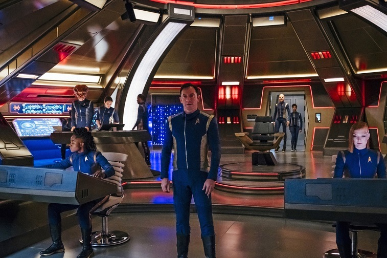 A man stands on a craft surrounded while other people sit at screens beside him in Star Trek: Discovery