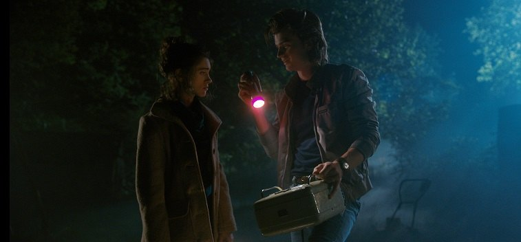 Nancy and Steve stand next to each other in a dark night in Stranger Things 2