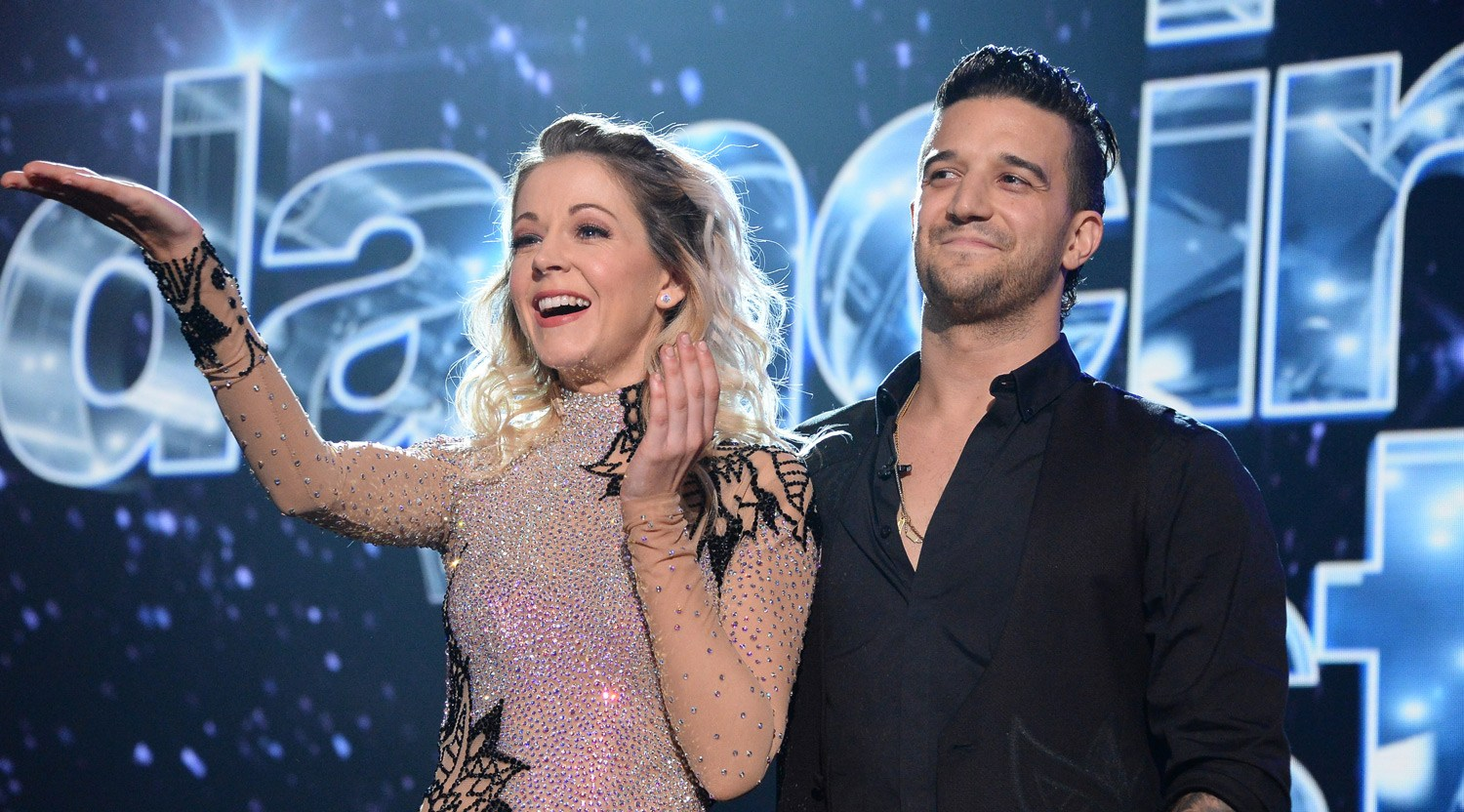 Lindsey Stirling and Mark Ballas stand next to each other on the stage