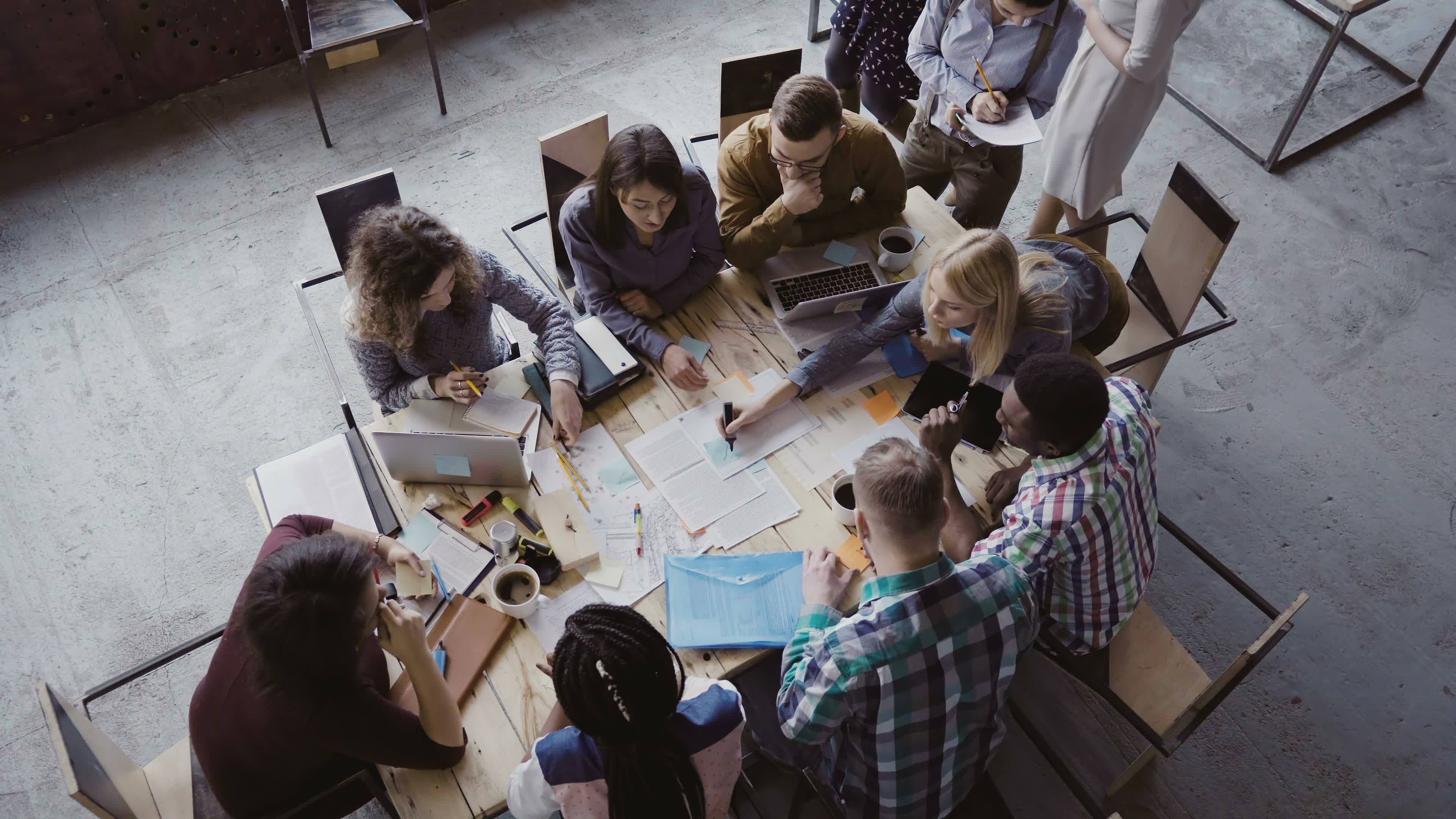 Top view of mixed race business team sitting at the table at loft office and working. Woman manager brings the document