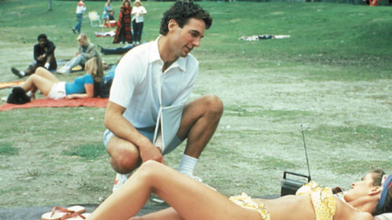Mark Harmon as Ted Bundy in The Deliberate Stranger talking to a sunbathing woman in a park