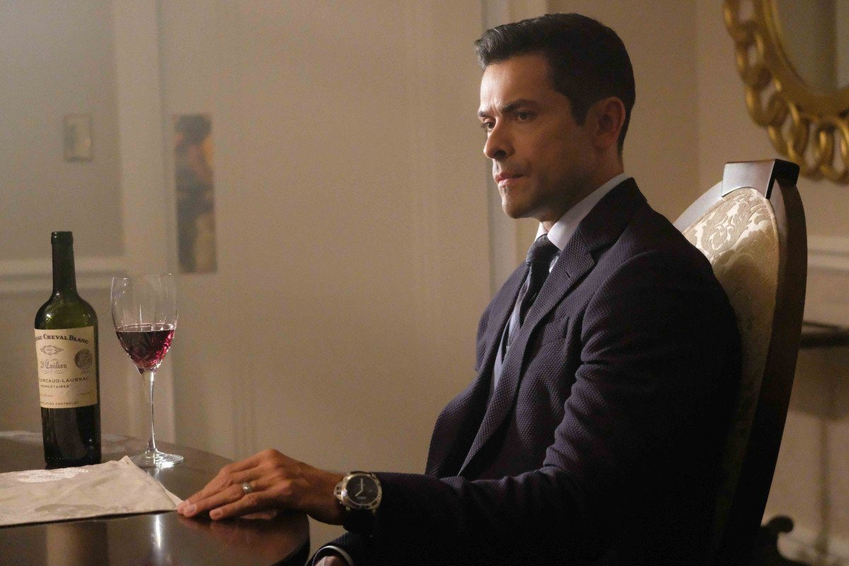 Mark Consuelos as Hiram Lodge sits in a suit at a dining room table in front of a glass of wine