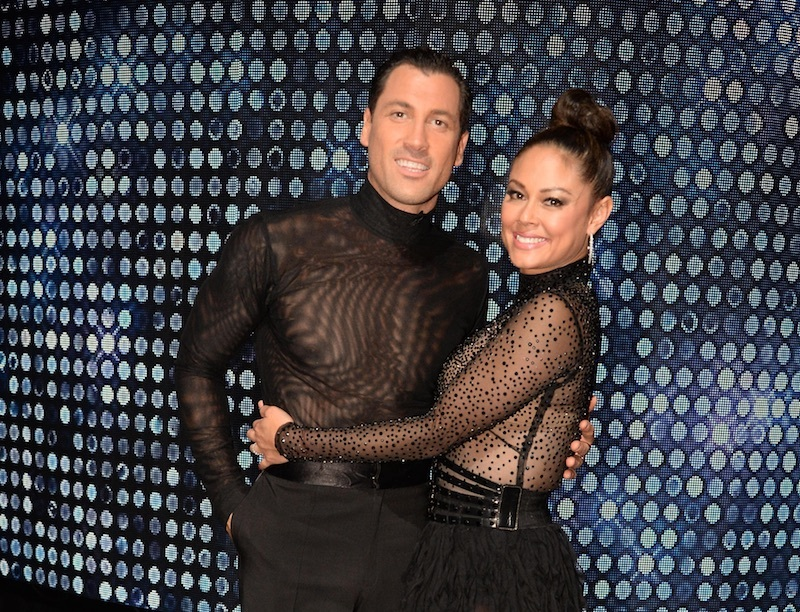 Maksim Chmerkovskiy and Vanessa Lachey smile and hug while wearing black costumes
