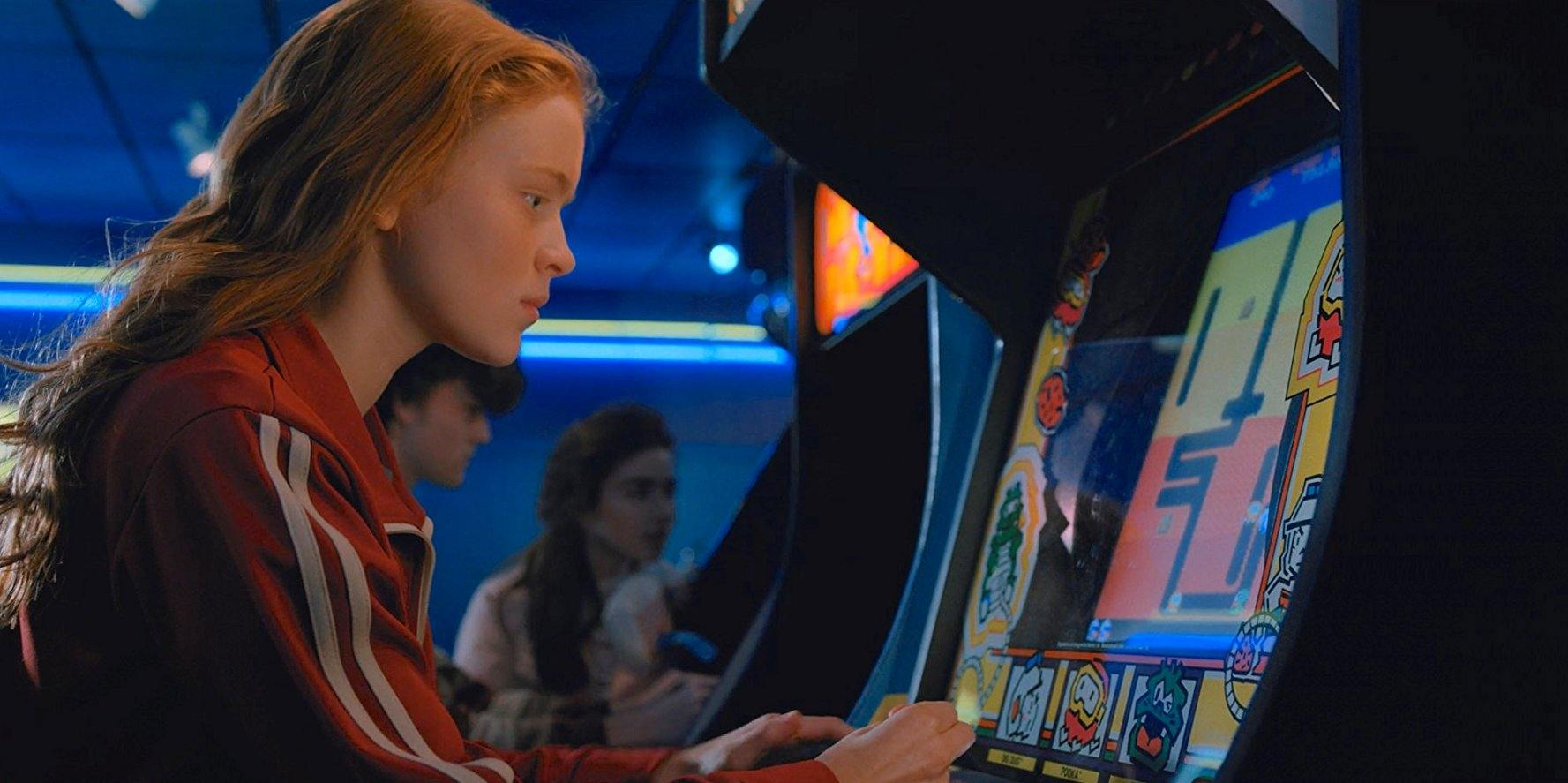 Sadie Sink as Max playing an old-fashioned video game machine in Stranger Things 2