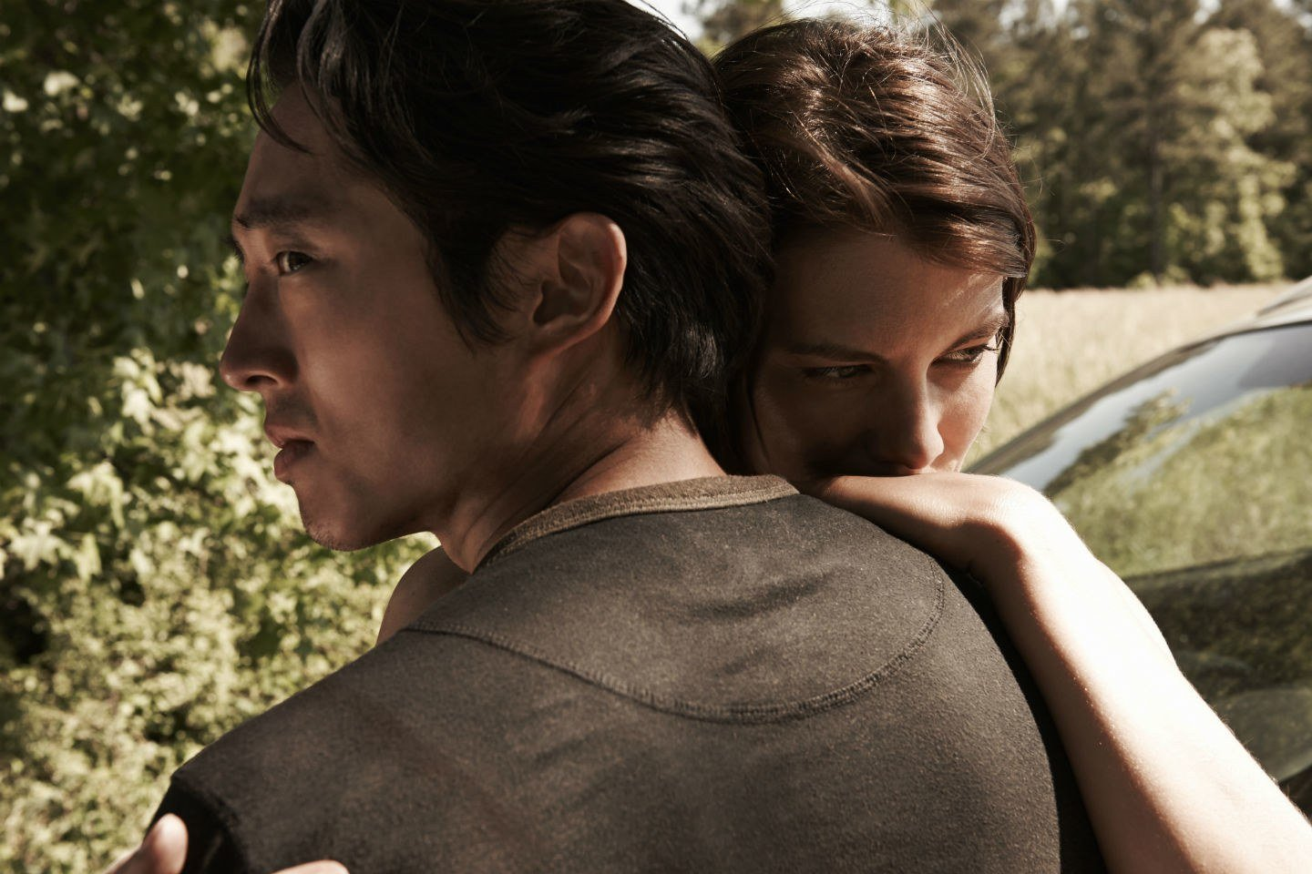 Glenn hugs Maggie while standing in front of trees
