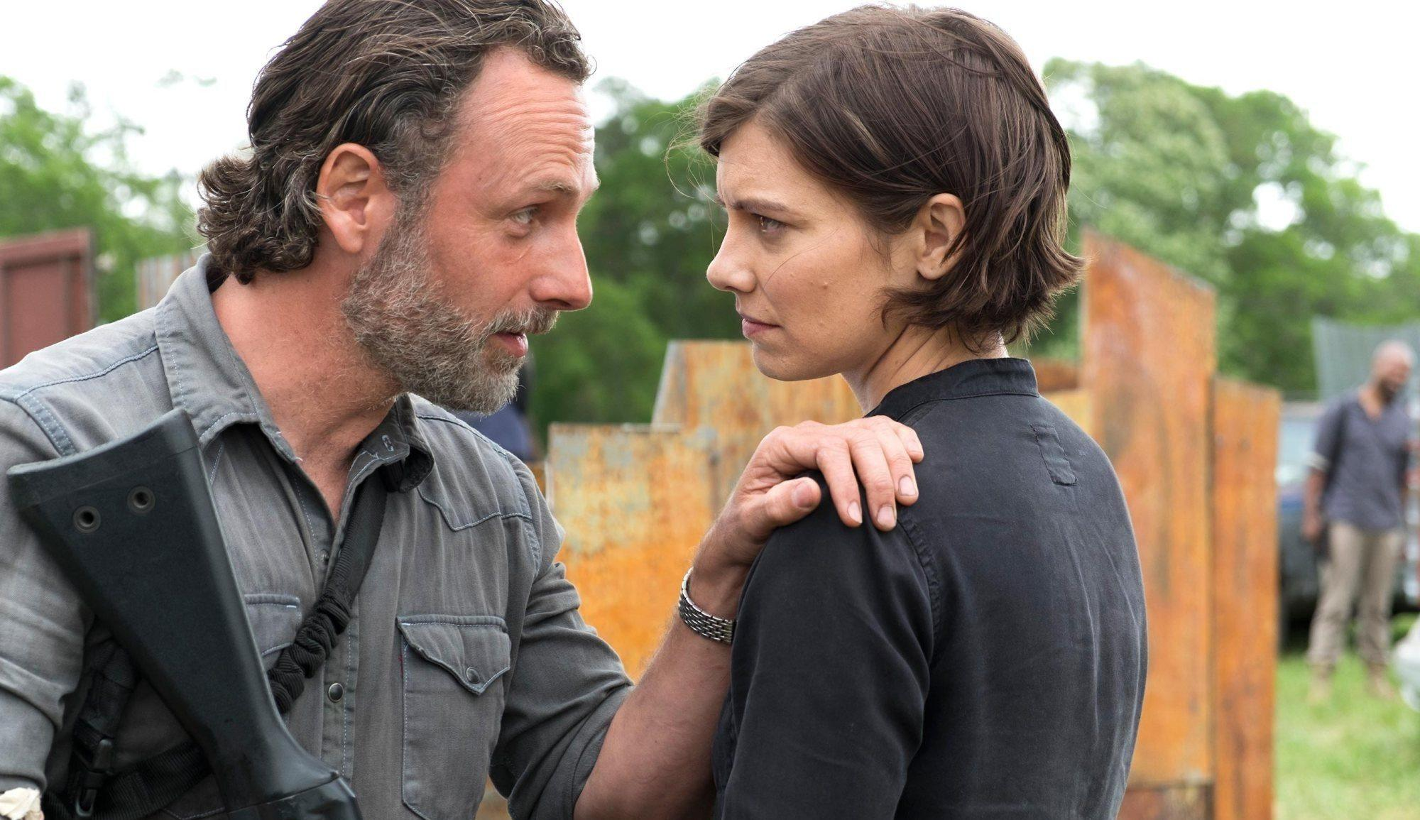 Rick puts his hand on Maggie's shoulder and holds a gun in another hand