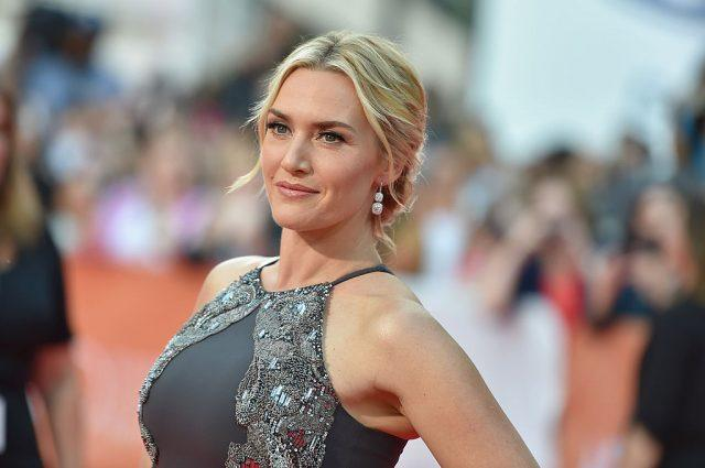 Kate Winslet posing for the paparazzi in a gray gown.