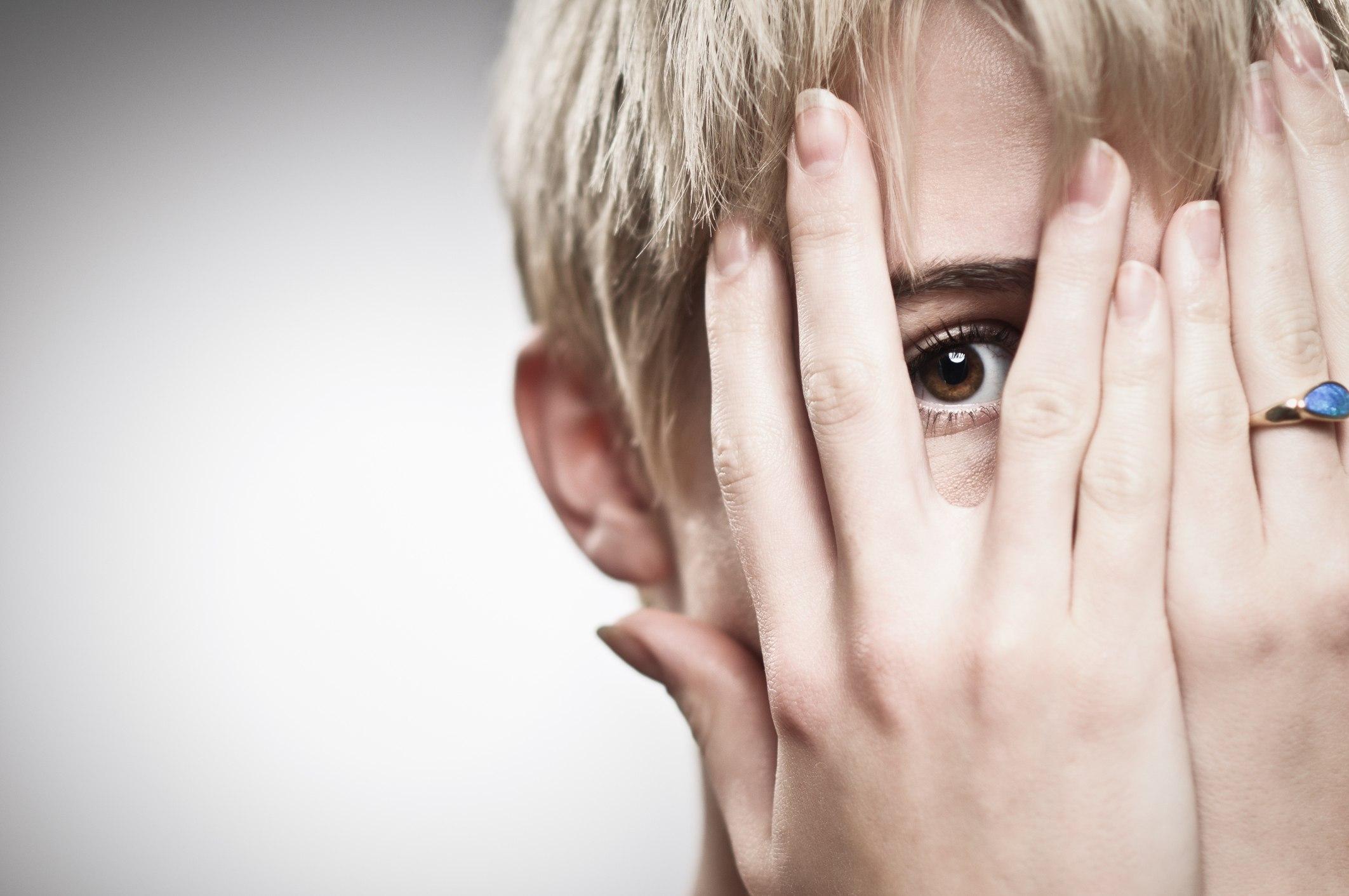 Woman peeking through fingers