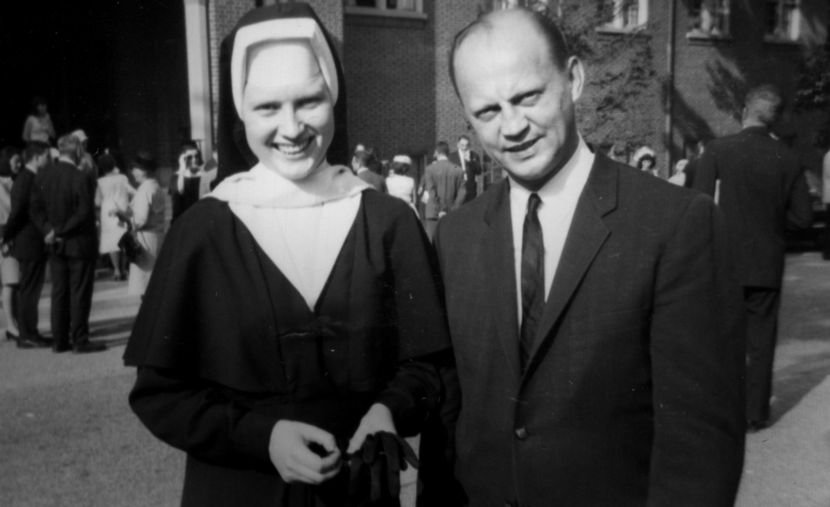 A nun and a man in a suit smile for a photograph.