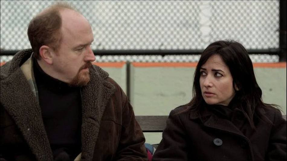 Louie and Pamela sit next to each other and look at each other