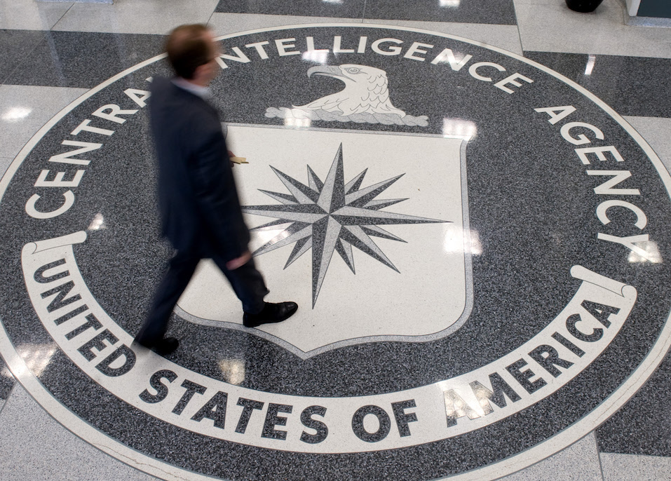 A man crosses the Central Intelligence Agency logo